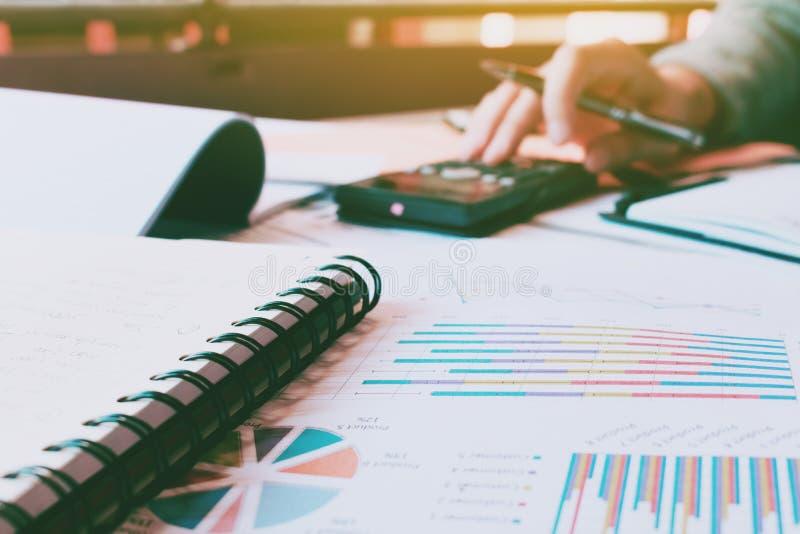 El hacer de la mano de la mujer calcula finanzas con papeleo en el escritorio y el th imágenes de archivo libres de regalías
