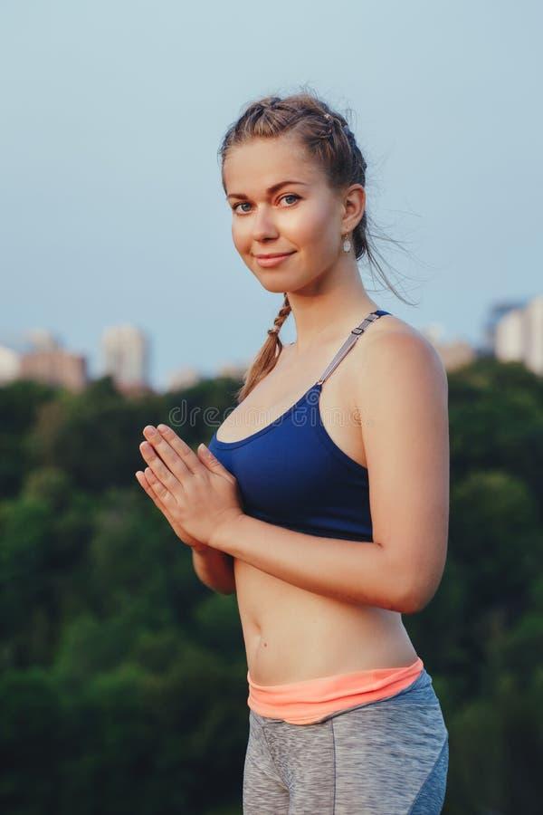 El hacer de la mujer ruega actitud de la yoga en parque al aire libre en la puesta del sol imagenes de archivo