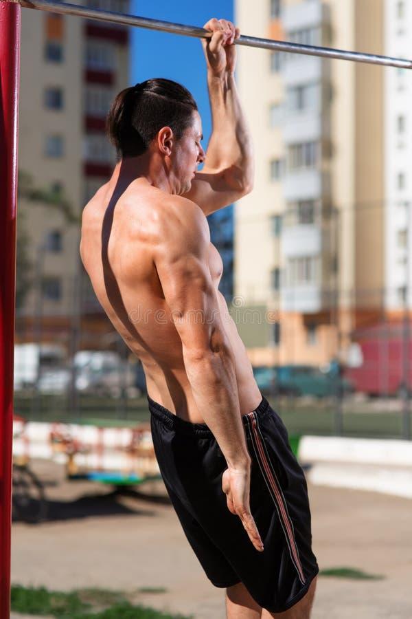 El hacer muscular joven del atleta levanta los ejercicios que cuelgan con una mano recta en una barra horizontal Fotos de la part fotografía de archivo