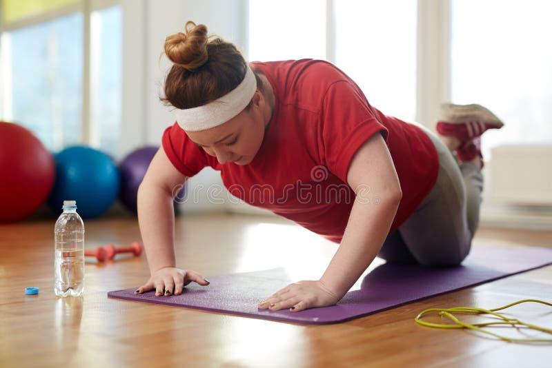 El hacer obeso de la mujer empuja hacia arriba ejercicios para perder el peso imágenes de archivo libres de regalías