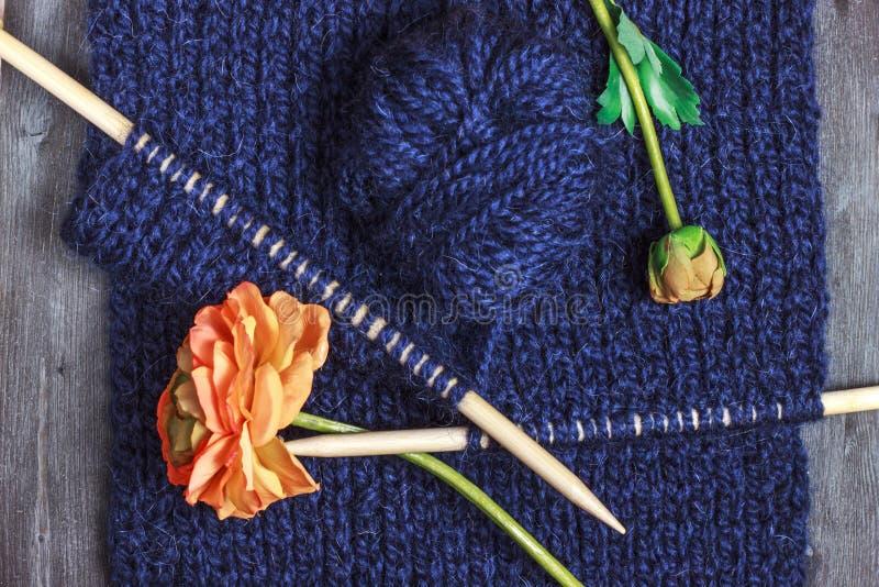 El hacer punto con la bola de madera de las agujas que hacen punto y del hilado de lanas en azul foto de archivo