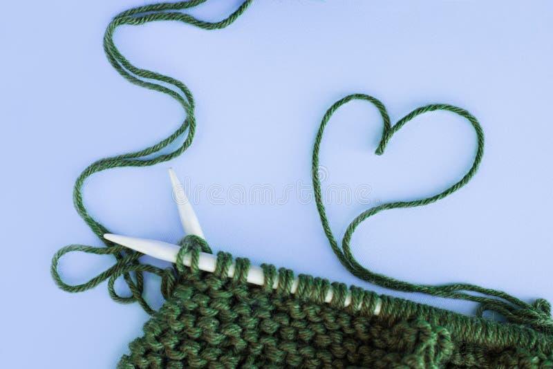 El hacer punto, costura, corazón del hilado, bufanda y sombrero con un verde del pompón, flatlay, espacio para el texto, espacio  foto de archivo libre de regalías