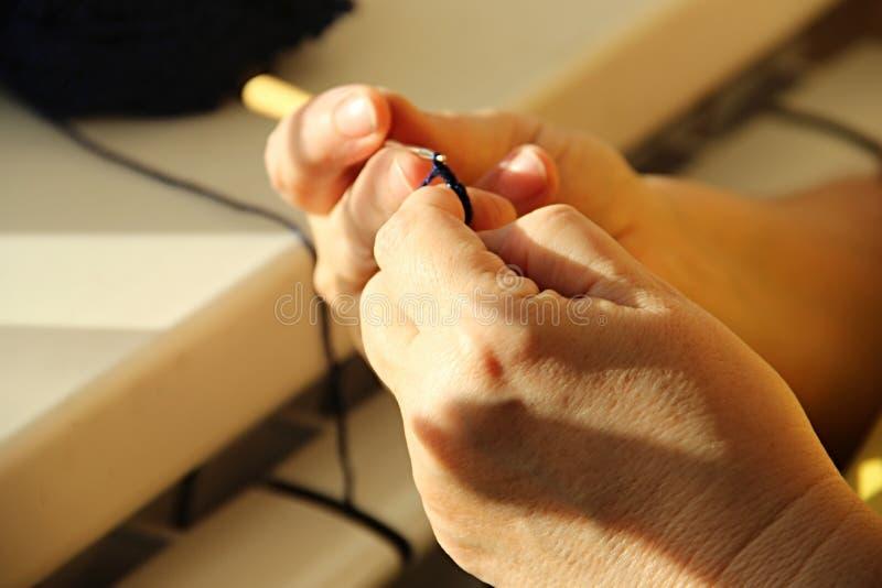 El hacer punto de las manos del ` s de la mujer mayor los puntos de la mujer mayor hecho a ganchillos del hilado azul marino Flor fotografía de archivo libre de regalías