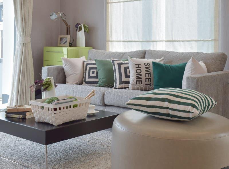 El hacer punto determinado en sala de estar acogedora con el sofá gris y las almohadas retras imagenes de archivo