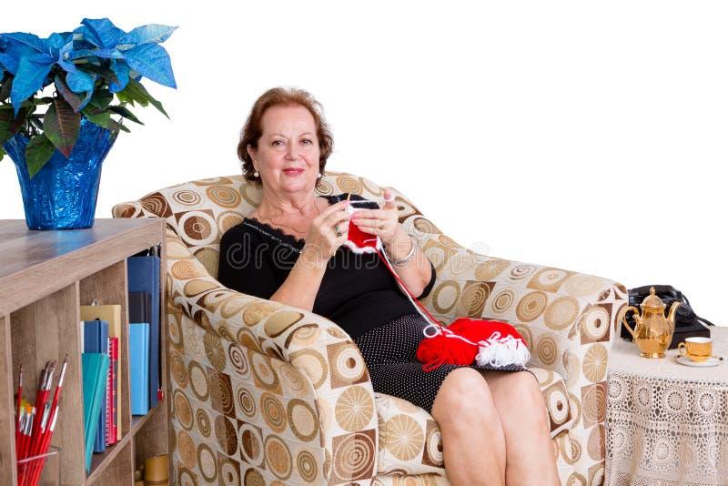 El hacer punto que se sienta de la señora mayor elegante en casa fotografía de archivo libre de regalías