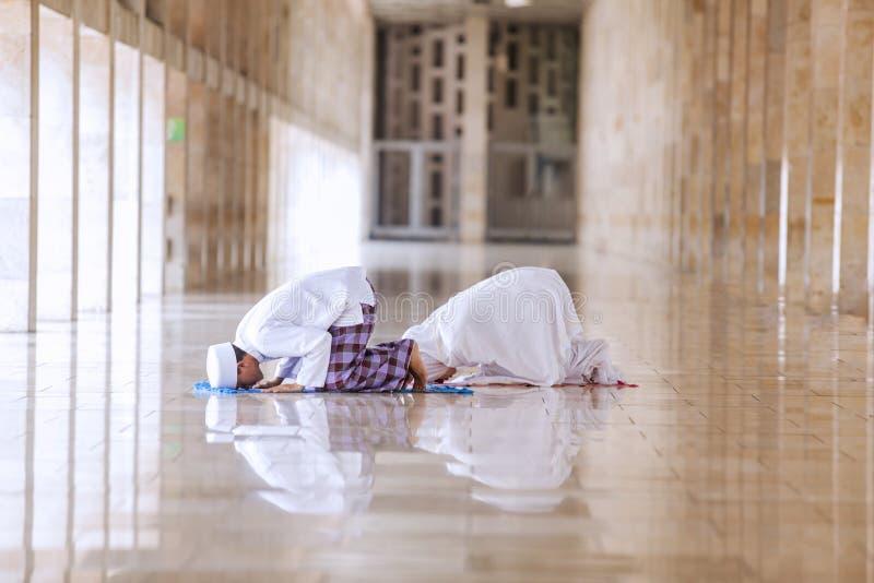 El hacer religioso de los pares ruega en la mezquita foto de archivo