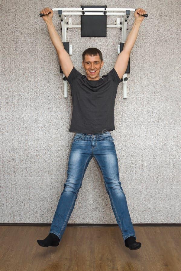 El hacer sonriente feliz del hombre joven levanta ejercicios en barra horizontal en su hogar imágenes de archivo libres de regalías