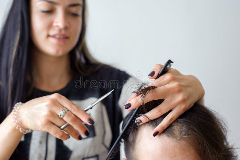El hairstyling de los hombres y el haircutting en un salón de la peluquería de caballeros o de pelo fotos de archivo libres de regalías