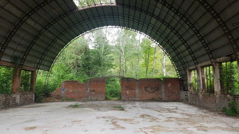 El hangar destruido fue crecido demasiado con los arbustos foto de archivo