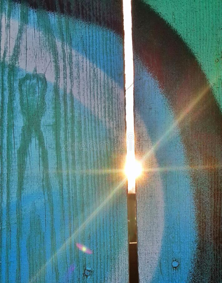El haz del sol a través de la cerca foto de archivo