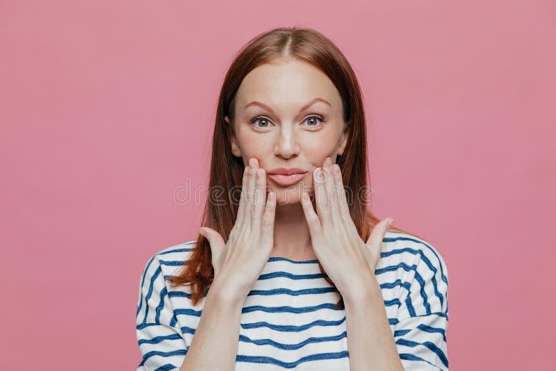 El Headshot de la mujer bonita pecosa guarda las manos cerca de los labios, tiene mínimo compone, piel sana, pelo marrón, demuest imagenes de archivo