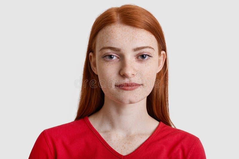 El Headshot de la mujer europea pelirroja atractiva con la piel pecosa, mira seriamente la cámara, tiene mínimo compone, lleva ro foto de archivo