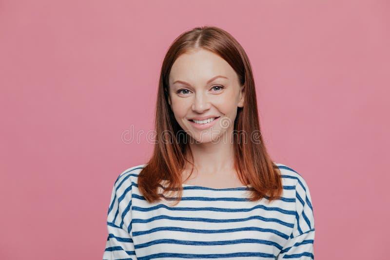 El Headshot de la mujer europea sonriente bonita con sonrisa encantadora, lleva el puente rayado, tiene pelo marrón, mira directa fotos de archivo