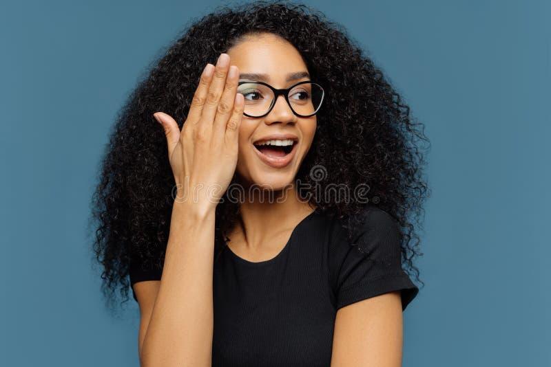 El Headshot de la mujer rizada hermosa mira a un lado, toca la cara, lleva los vidrios transparentes, camiseta casual negra, aisl fotografía de archivo libre de regalías