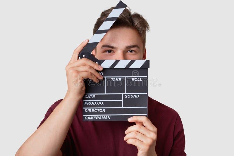 El Headshot del hombre hermoso oculta la cara con el tablero de chapaleta, mira seriamente la cámara, vestida en camiseta casual, imagenes de archivo
