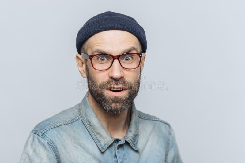 El Headshot del varón sin afeitar apuesto con los ojos azules, miradas con la expresión sorprendida en cámara, siente emocionado  fotos de archivo