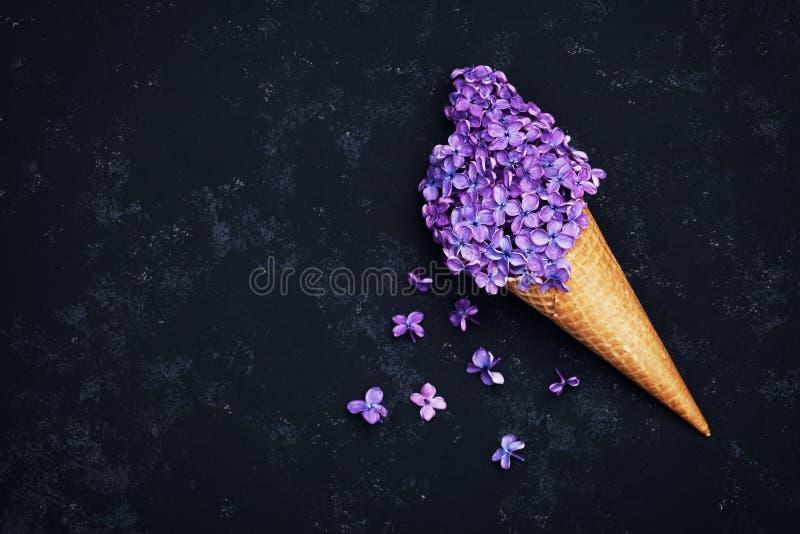 El helado de la lila florece en cono de la galleta en fondo negro desde arriba, arreglo floral hermoso, color del vintage, comple foto de archivo libre de regalías