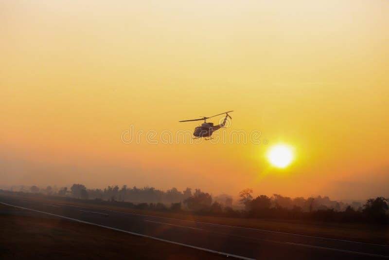 El helicóptero de la silueta saca de pista del aeropuerto de Mae Sot en w fotos de archivo