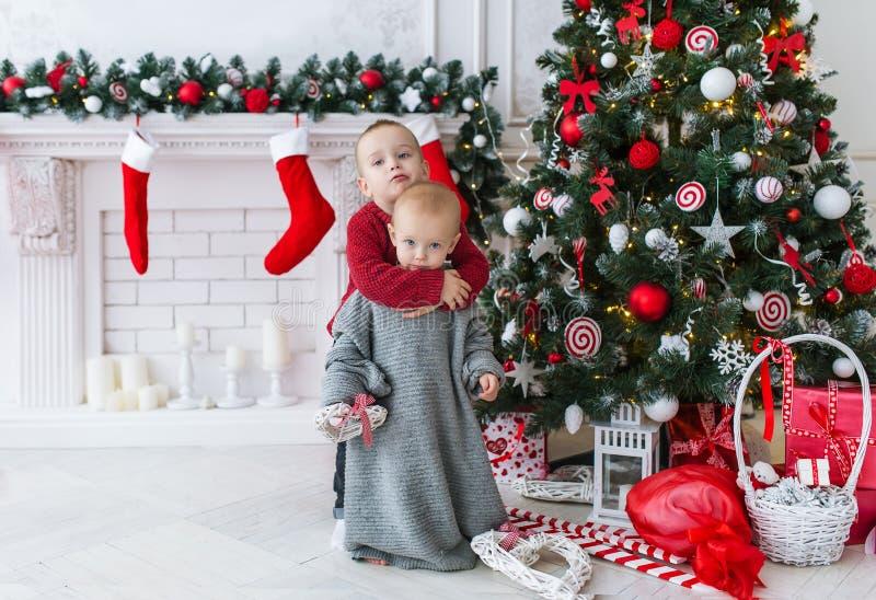 El hermano abraza a la pequeña hermana en día de la Navidad imagen de archivo