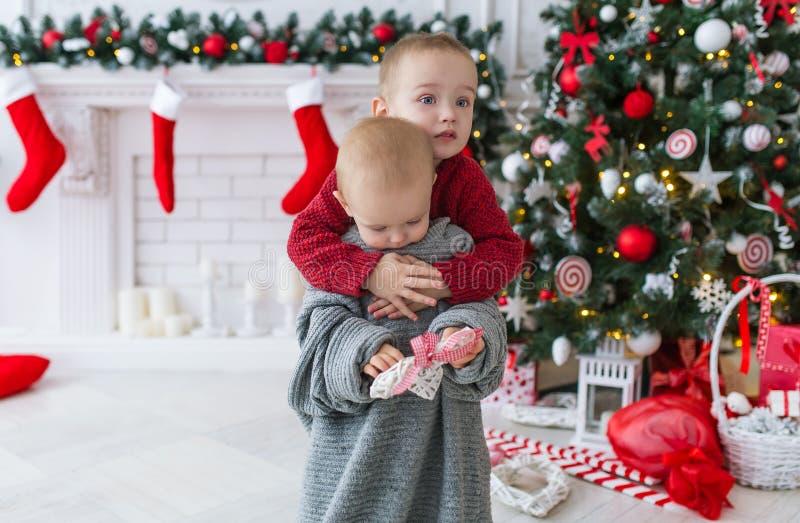 El hermano abraza a la pequeña hermana en día de la Navidad fotos de archivo libres de regalías