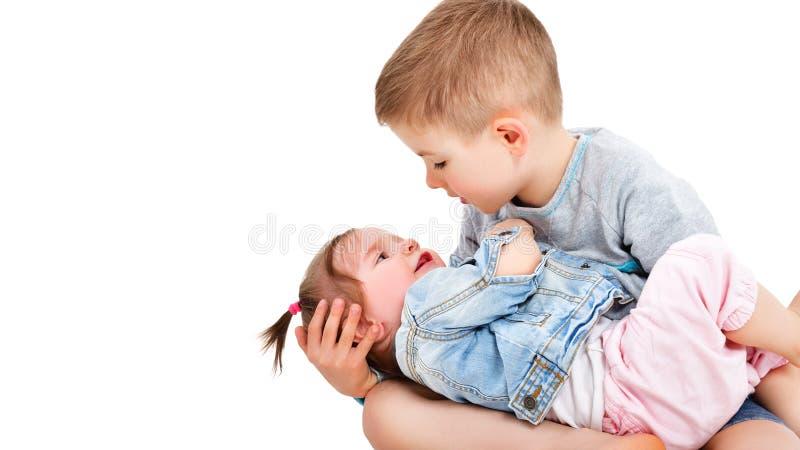 El hermano mira en los ojos de su pequeña hermana linda imagenes de archivo
