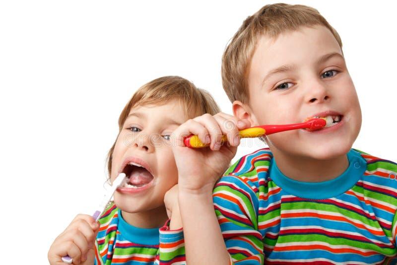 El hermano y la hermana en camisas aplican sus dientes con brocha imagen de archivo