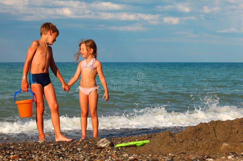 El hermano y la hermana llevan a cabo las manos y se colocan en la playa fotos de archivo libres de regalías