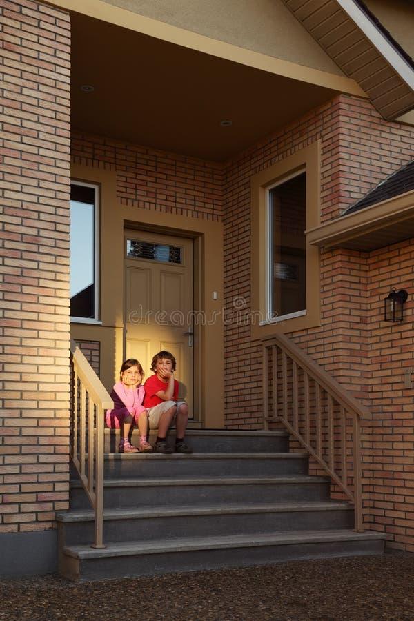El Hermano Y La Hermana Se Sientan En Las Escaleras Cerca De Puerta Foto de archivo