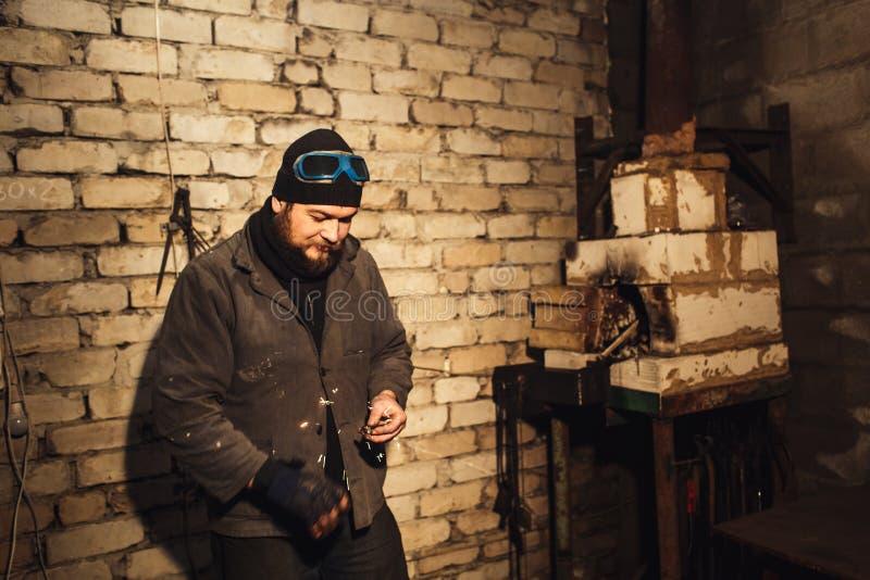 El herrero barbudo enciende el fuego con el firesteel y el pedernal imagenes de archivo