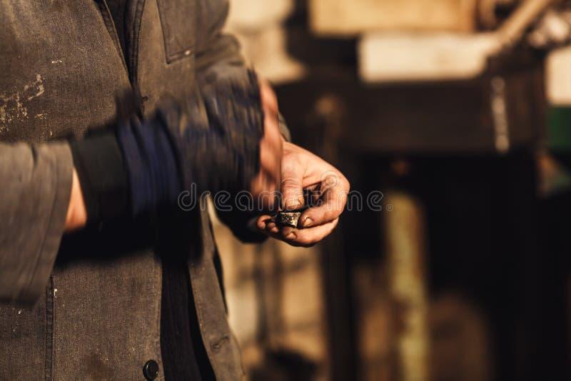 El herrero enciende el fuego con el firesteel y el pedernal fotos de archivo