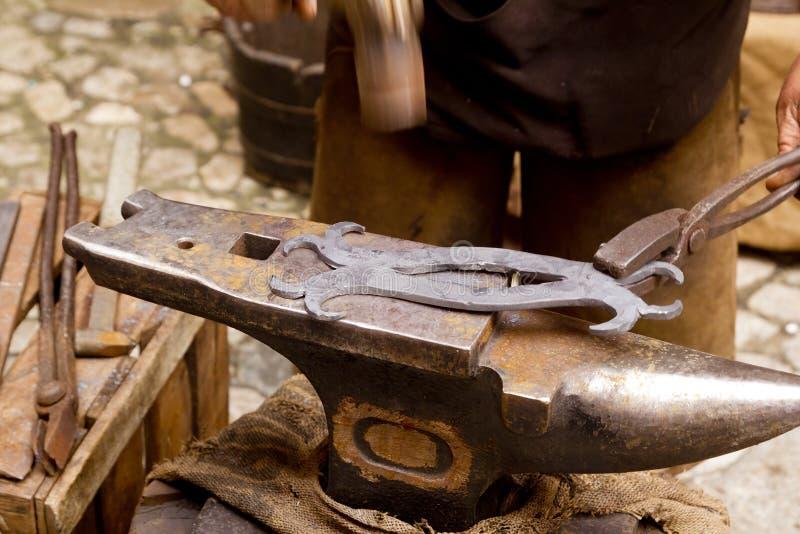 El herrero forjó el yunque del forjador del hierro hammerman foto de archivo