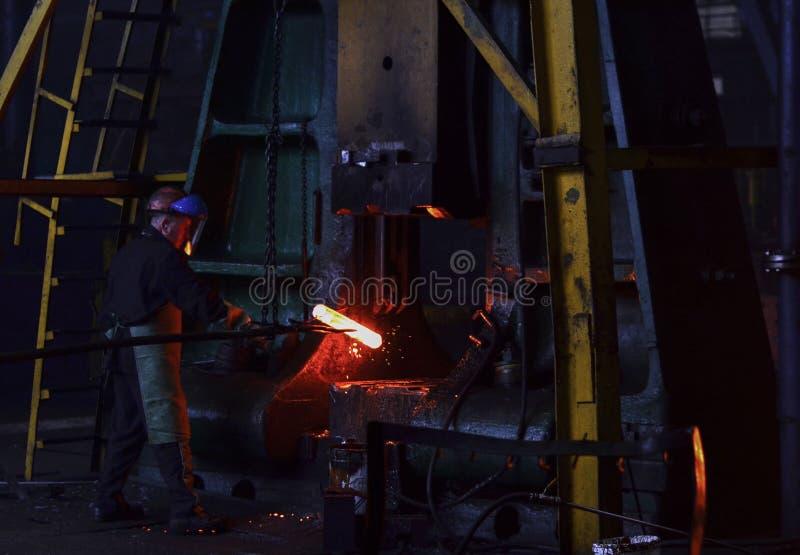 El herrero procesa el producto del hierro debajo de una prensa enorme, forjando el metal, sellando imagenes de archivo