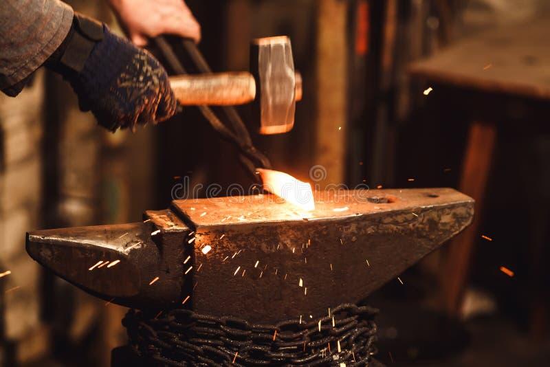 El herrero que forja manualmente el metal candente en el yunque en herrería con los fuegos artificiales de la chispa fotografía de archivo