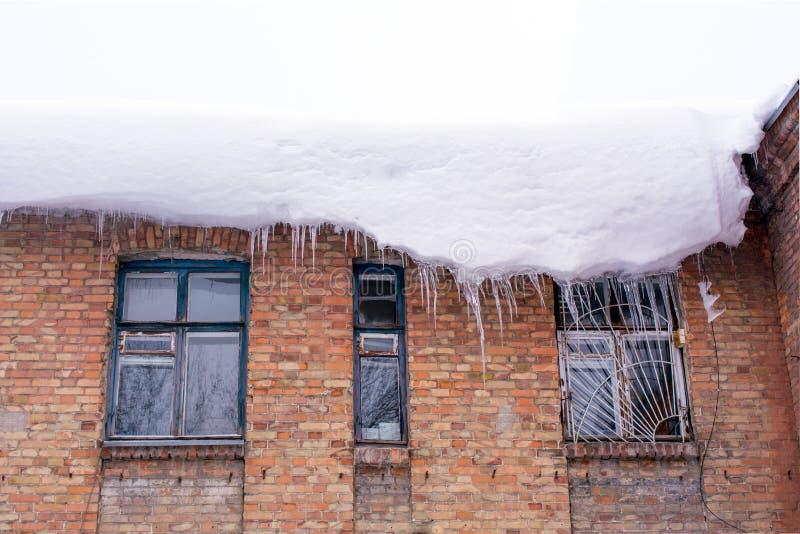 El hielo de la nieve cuelga de un tejado fotografía de archivo