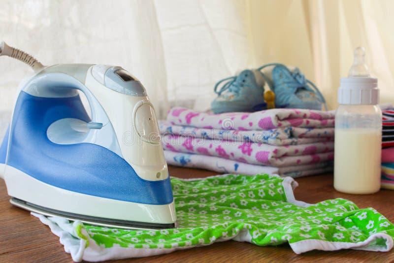 El hierro frota ligeramente la camiseta de los niños En el fondo, los pañales, bebé visten, pacificador, pequeños zapatos imagen de archivo libre de regalías