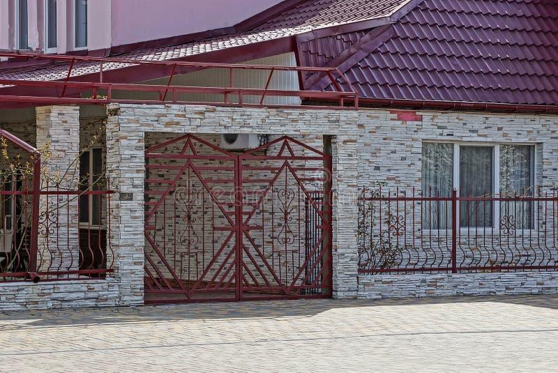 El hierro rojo cerró las puertas con una cerca y una parte de una casa gris con una ventana imagen de archivo libre de regalías