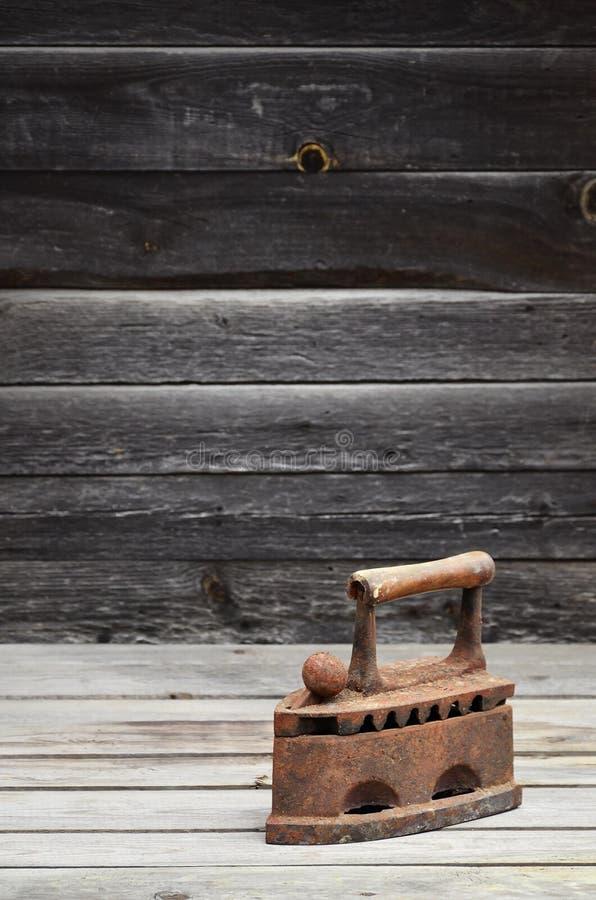 El hierro viejo pesado y oxidado del carbón miente en una superficie de madera foto de archivo
