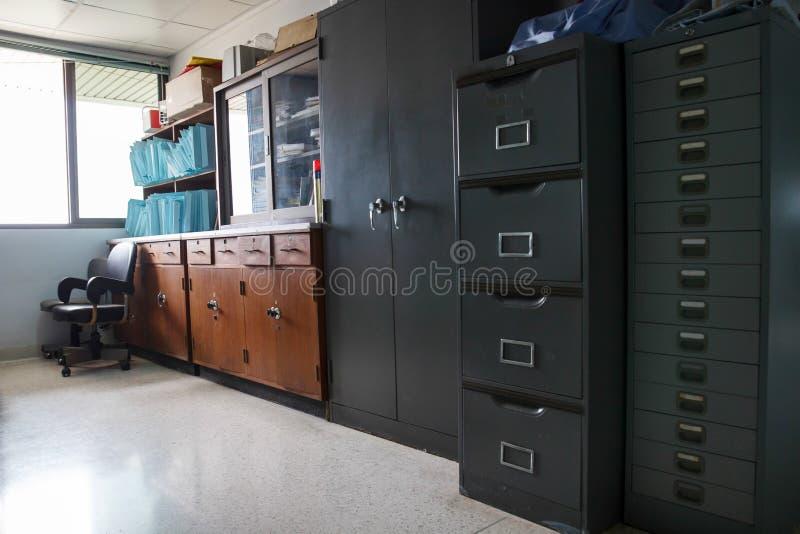 El hierro viejo y el gabinete de madera para guardar el documento reservan imagenes de archivo