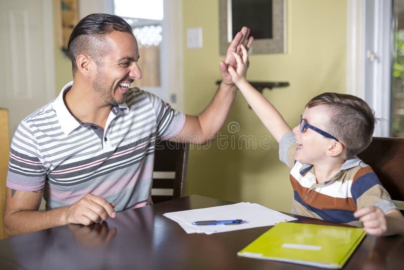 El hijo de ayuda del padre hace la preparación El padre ayuda a su niño fotos de archivo