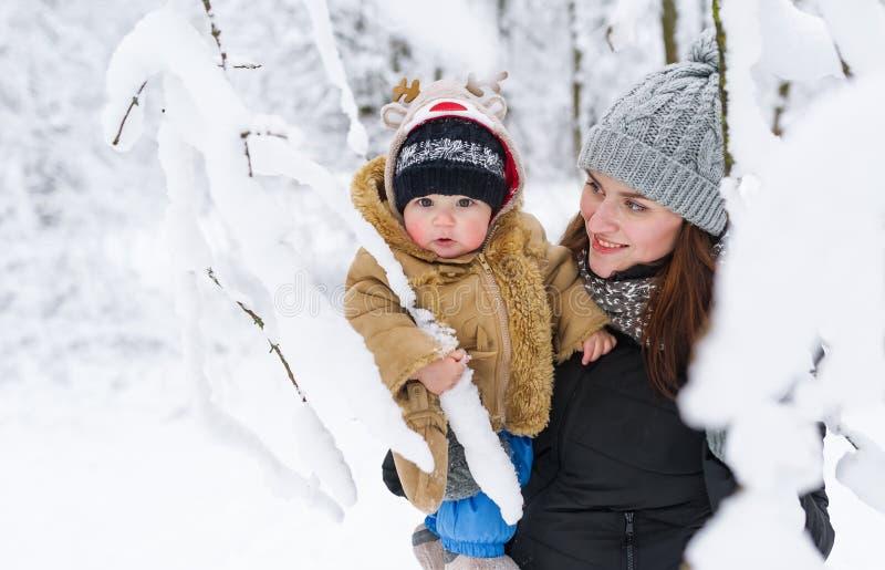 El hijo de la madre y del bebé que abraza en un invierno parquea entre ramas de árboles fotos de archivo libres de regalías