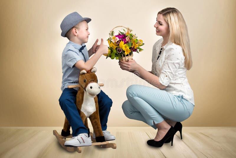El hijo en el caballo, da una cesta de madre querida de las flores Pequeño príncipe a caballo Primavera, día del ` s de las mujer foto de archivo libre de regalías