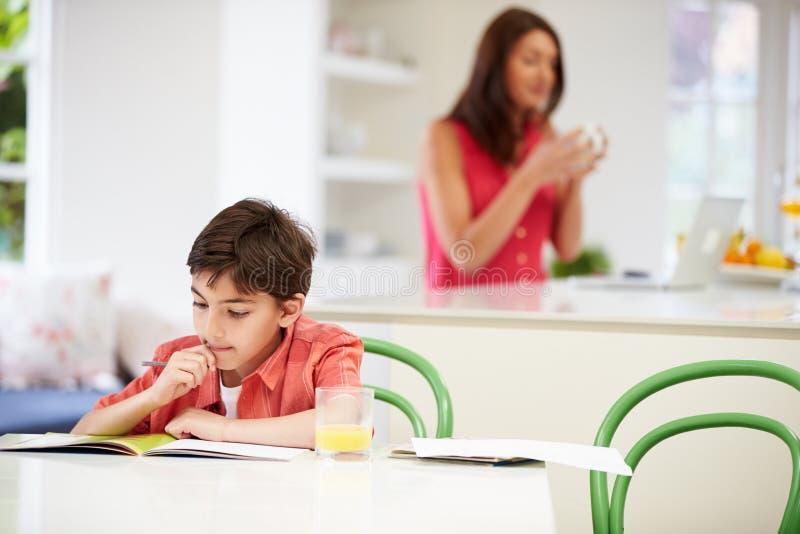 El hijo hace la preparación mientras que la madre utiliza el ordenador portátil fotos de archivo