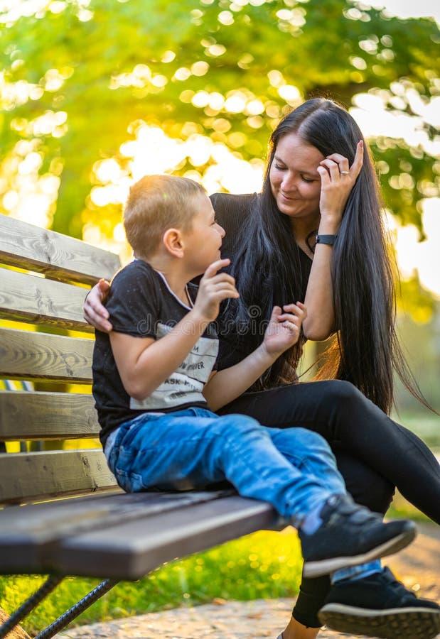 El hijo que esmalta en su ` s de la madre observa en un banco de parque en Autum Colorf imagenes de archivo