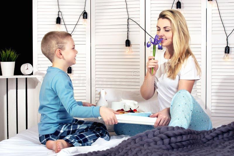 El hijo traer para el desayuno de la madre en cama Un buen comienzo al día Día del `s de la madre Día del ` s de la mujer imagen de archivo libre de regalías