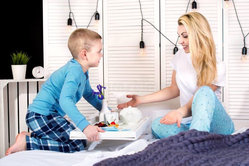El hijo trajo su desayuno de la madre en cama Un buen comienzo al día Día del `s de la madre Día del ` s de la mujer imagen de archivo libre de regalías