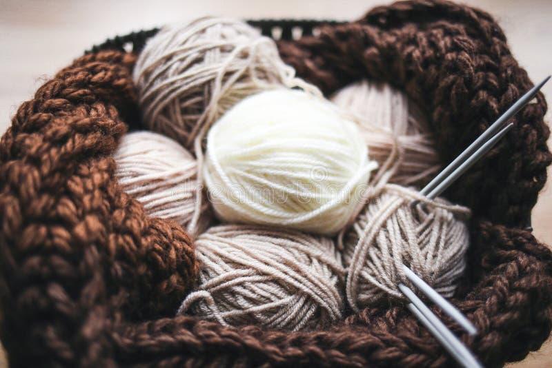 El hilado beige, las agujas que hacen punto y una bufanda marrón están en la cesta fotos de archivo