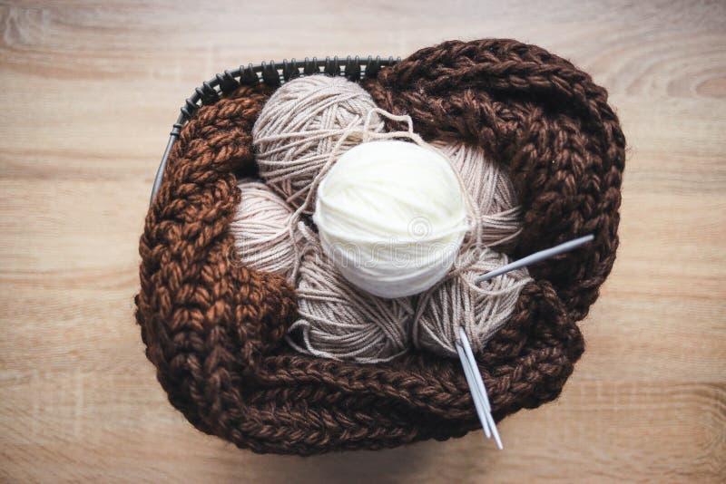 El hilado beige, las agujas que hacen punto y una bufanda marrón están en la cesta imágenes de archivo libres de regalías