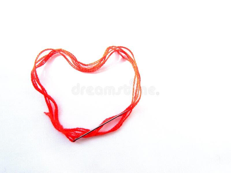El hilo grueso de las lanas rojas brillantes con una aguja de costura miente en la forma de un objeto aislado corazón en un fondo imagenes de archivo