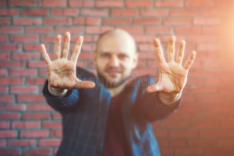 El hipnotizador o el hombre de negocios joven en una chaqueta que sonríe y que muestra da extendido adelante con las palmas imagen de archivo libre de regalías