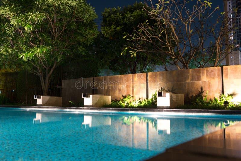 El hogar costoso con la piscina de lujo del diseñador y el agua caen imagen de archivo